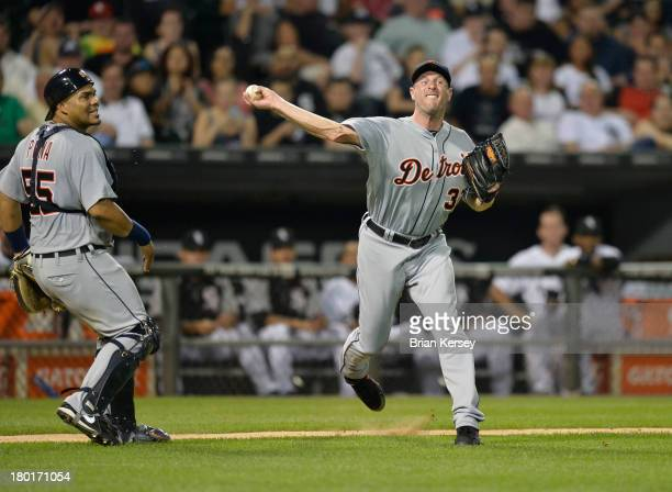 Starting pitcher Max Scherzer of the Detroit Tigers throws to first to try and retire Josh Phegley of the Chicago White Sox after he hit a slow...