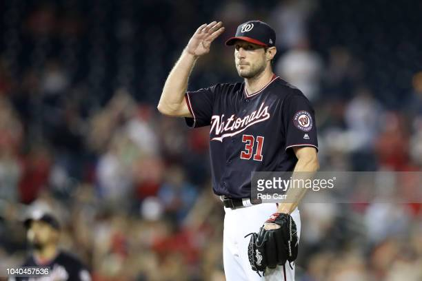 Starting pitcher Max Scherzer of the Washington Nationals acknowledges the crowd after recording his 300th strikeout for the year against the Miami...