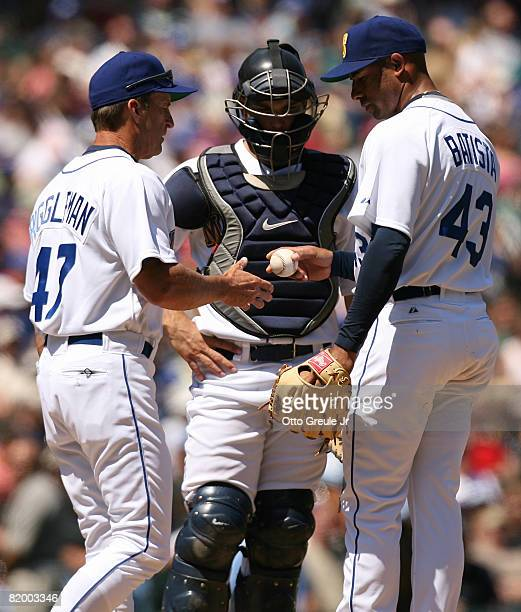Starting pitcher Miguel Batista of the Seattle Mariners is removed from the game by manager Jim Riggleman as Catcher Jeff Clement looks on against...