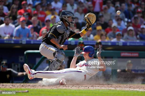 Starting pitcher Nick Pivetta of the Philadelphia Phillies slides safely into home plate as catcher Elias Diaz of the Pittsburgh Pirates fields the...