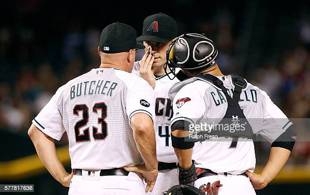 Starting pitcher Patrick Corbin of the Arizona Diamondbacks talks with pitching coach Mike Butcher and catcher Welington Castillo during a mound...