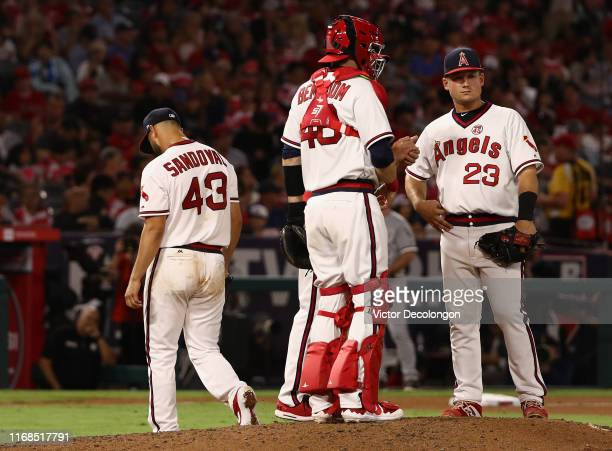 Starting pitcher Patrick Sandoval of the Los Angeles Angels leaves the game as catcher Anthony Bemboom and Matt Thaiss look on during the fourth...
