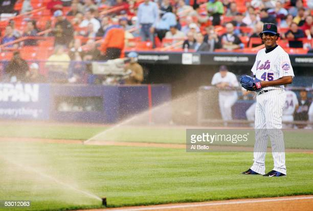 Starting pitcher Pedro Martinez of the New York Mets laughs after the sprinklers turned on during the game against the Arizona Diamondbacks in the...