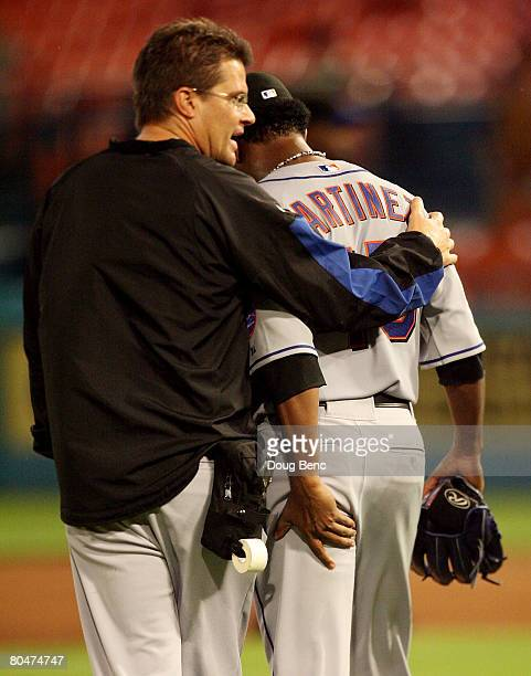 Starting pitcher Pedro Martinez of the New York Mets talks with a trainer after a hamstring injury in the fourth inning against the Florida Marlins...