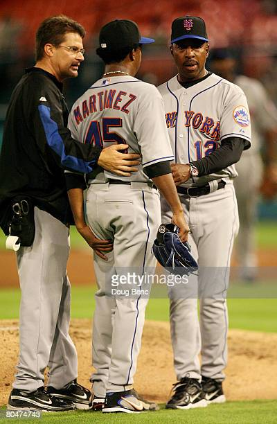 Starting pitcher Pedro Martinez of the New York Mets talks with a trainer and manager Willie Randolph after a hamstring injury in the fourth inning...