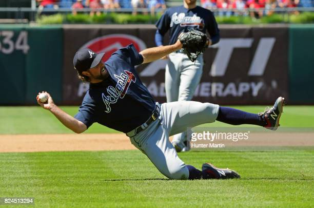 Starting pitcher RA Dickey of the Atlanta Braves attempts to make a throw to first base after fielding a ground ball in the fourth inning during a...