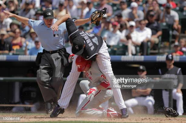 Starting pitcher Roy Halladay of the Philadelphia Phillies slides home safely under the tag of starting pitcher Jason Hammel of the Colorado Rockies...