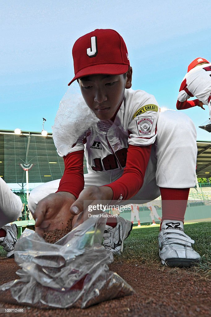 Starting pitcher Ryusuke Ikeda #14 of the Japan Little League team collects dirt from the pitchers mound after the game against the United States on August 29, 2010 in South Willamsport, Pennsylvania. Japan won the Little League World Series Championship 4-1.