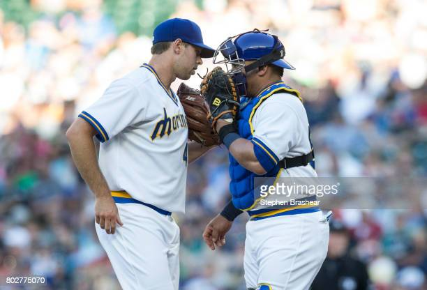 Starting pitcher Sam Gaviglio of the Seattle Mariners and catcher Carlos Ruiz meet at the mound during a game against the Houston Astros at Safeco...