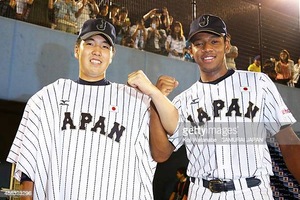 Starting pitcher Sena Sato and Outfielder Louis Okoye of Japan pose for a photograph after winning in the super round game between Japan v Canada...