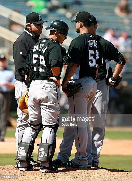 Starting pitcher Sergio Mitre of the Florida Marlins talks with pitching coach Mark Wiley before being pulled with elbow discomfort while taking on...