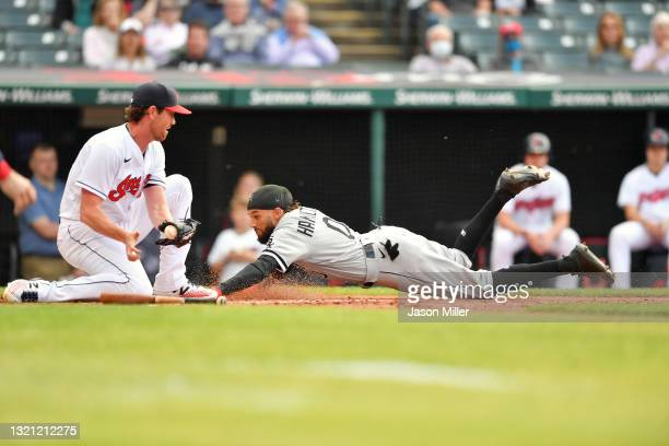 Starting pitcher Shane Bieber of the Cleveland Indians tries to tag Billy Hamilton of the Chicago White Sox who scored on an error during the second...