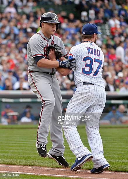 Starting pitcher Travis Wood of the Chicago Cubs tags out Kris Medlen of the Atlanta Braves after he laid down a sacrifice bunt during the seventh...