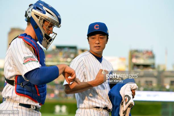 Starting pitcher Tsuyoshi Wada of the Chicago Cubs goes over the signs with catcher John Baker as they walk in from the bullpen before the game...