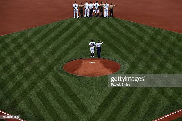 Starting pitcher Tyler Wilson of the Baltimore Orioles and teammates stand with members of the United States Armed Forces before playing against the...