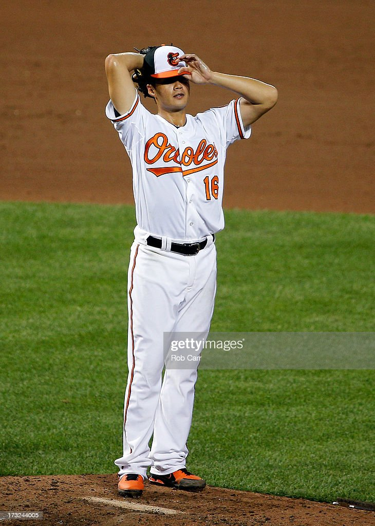 Starting pitcher Wei-Yin Chen #16 of the Baltimore Orioles adjusts his cap against the Texas Rangers in the seventh inning of the Orioles 6-1 win at Oriole Park at Camden Yards on July 10, 2013 in Baltimore, Maryland.