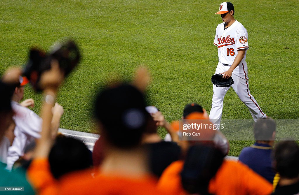 Starting pitcher Wei-Yin Chen #16 of the Baltimore Orioles walks to the dugout after retiring the side against the Texas Rangers in the seventh inning of the Orioles 6-1 win at Oriole Park at Camden Yards on July 10, 2013 in Baltimore, Maryland.