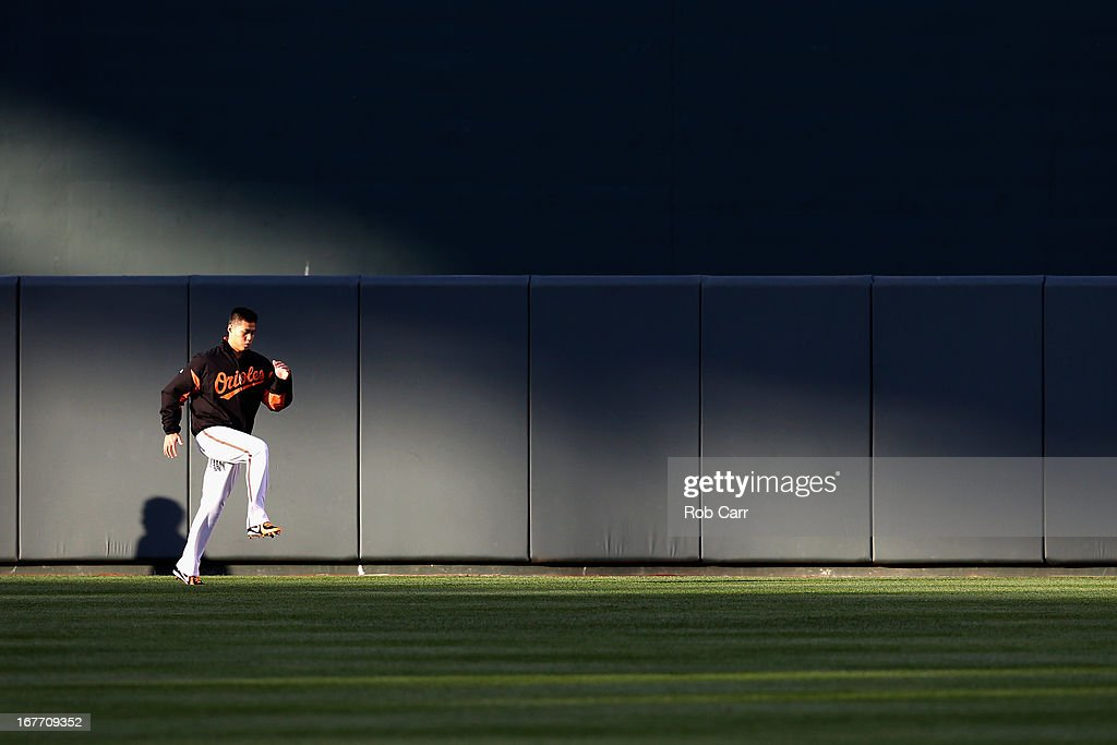 Starting pitcher Wei-Yin Chen #16 of the Baltimore Orioles warms up in the outfield before the start of the Orioles game against the Los Angeles Dodgers during game two of a double header at Oriole Park at Camden Yards on April 20, 2013 in Baltimore, Maryland.