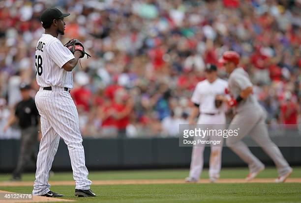 Starting pitcher Yohan Flande of the Colorado Rockies returns to the mound as Matt Adams of the St. Louis Cardinals rounds the bases on his two run...