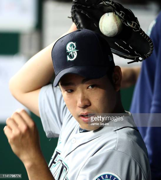 Starting pitcher Yusei Kikuchi of the Seattle Mariners stretches in the dugout during the game against the Kansas City Royals at Kauffman Stadium on...