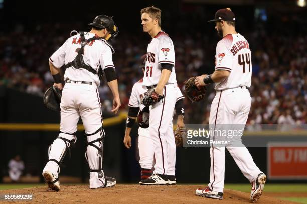 Starting pitcher Zack Greinke of the Arizona Diamondbacks talks with team mates Paul Goldschmidt and Jeff Mathis during the third inning of the...