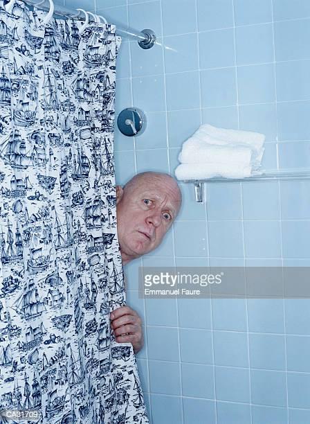 startled mature man stading in hotel room shower - maenner duschen stock-fotos und bilder