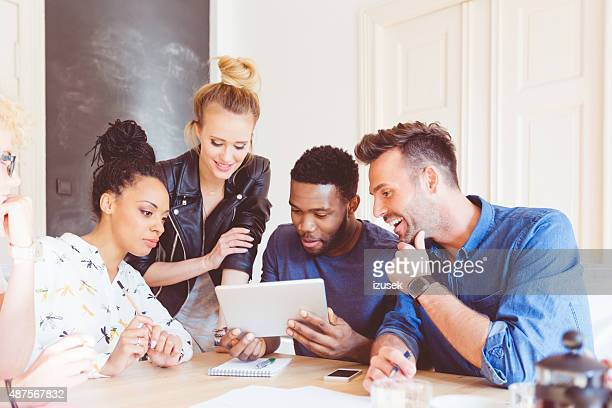 Start-up agency, multi ethnic team using digital tablet together