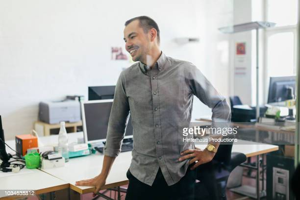 startup business office employee smiling - gray shirt stock pictures, royalty-free photos & images