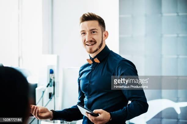 startup business owner talking to employees - anführen stock-fotos und bilder