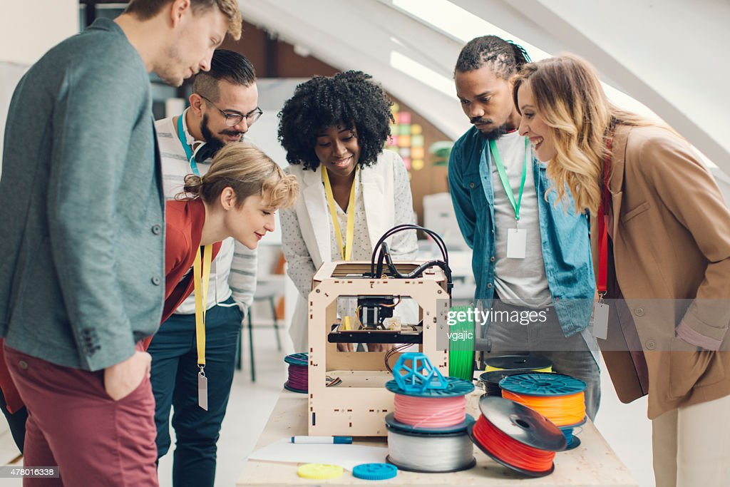 Inicialização equipe de negócios olhando para impressoras 3D. : Foto de stock