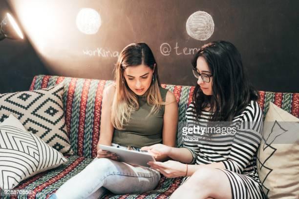 Start-Business-Team auf Sofa mit Tablette gegen Tafel Kreativbüro