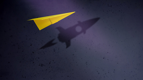 Start-up Company and Motivation in Business Concept. Paper Planes Flying with Shadow of Rocket over the Wall 1025252462
