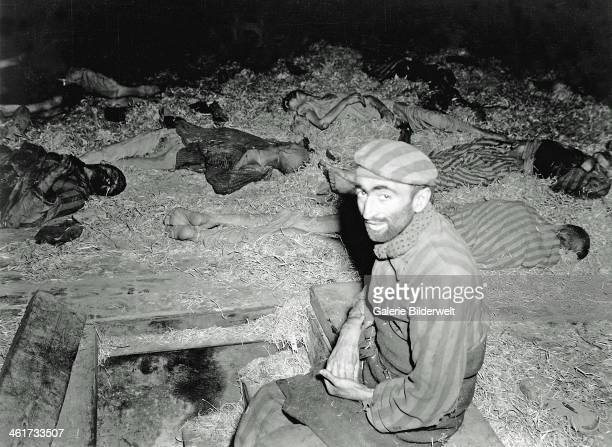 A starved Frenchman sits among the dead in a subcamp of the concentration camp MittelbauDora 12th April 1945 The camp was liberated by the 3rd...