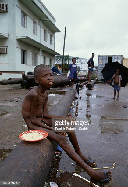 A starving child sits on a street in Monrovia one of thousands suffering from the severe food shortages Responding to years of government corruption...