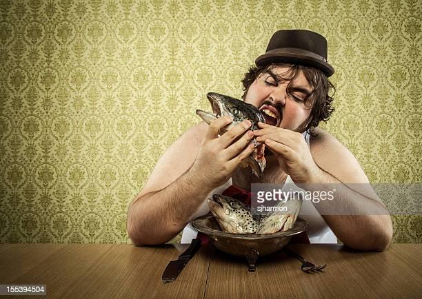starving fat man eating fish head soup at wood table