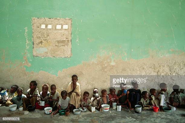 Starving Somali children sit in a row along a wall and eat from pots and bowls at an internationallyrun relief center In the 1980s warlord factions...