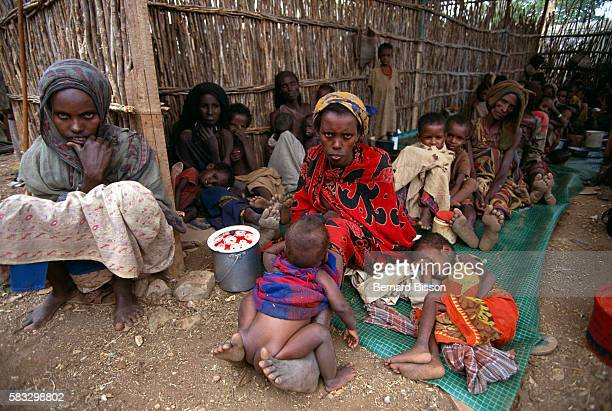 Starving Somalian children and mothers sit and lie on the ground They have been in this terrible situation since they had to flee and find a refuge...
