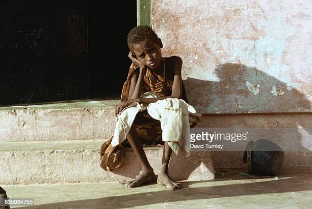 A starving young boy rests on a door stoop in Mogadishu