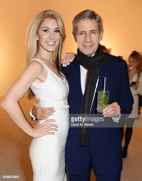 """Stasha Palos and Sir Stuart Rose attend a private view of """"And The Stars Shine Down"""" by Stasha Palos at the Saatchi Gallery on December 2, 2014 in..."""