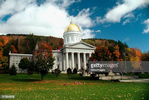 state capitol in the fall with blue sky & colorful trees in the background, montpelier, vermont - montpelier vermont stockfoto's en -beelden