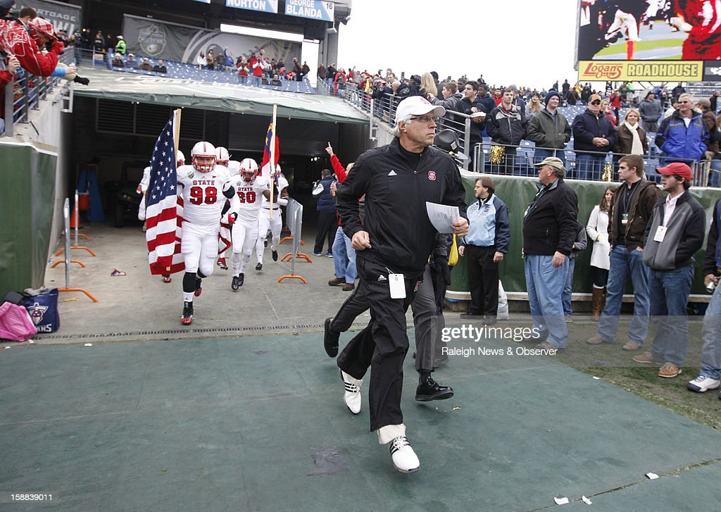 N.C. State defensive coordinator Mike Archer leads the team onto LP Field before the Wolfpack's game against Vanderbilt in the Franklin American Mortgage Music City Bowl in Nashville, Tennessee, Monday, December 31, 2012. The Vanderbilt Commodores defeated the N.C. State Wolfpack, 38-24.