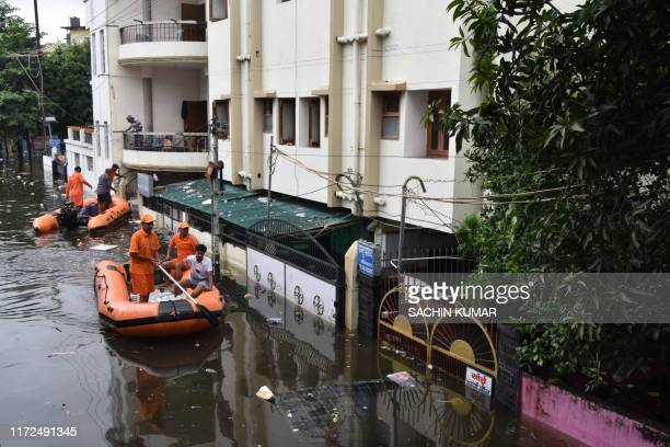 State Disaster Response Force personnel on boats travel along a flooded road of a residential neighborhood of Bahadurpur following heavy rainfalls in...
