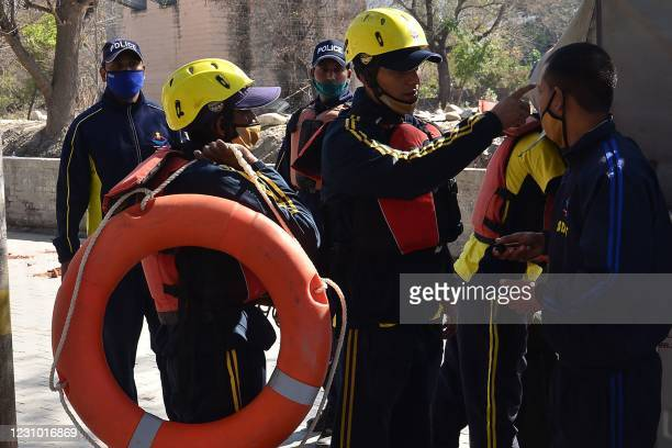 State Disaster Response Fund personnel prepare for deployment in Srinagar of Uttarakhand state on February 7, 2021 after a glacier broke off in...