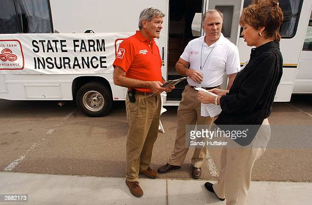 State Farm Insurance agents Charlie Pierce and Larry Gustavson help Scripps Ranch resident Sherry Collins with an insurance claim at a make shift...