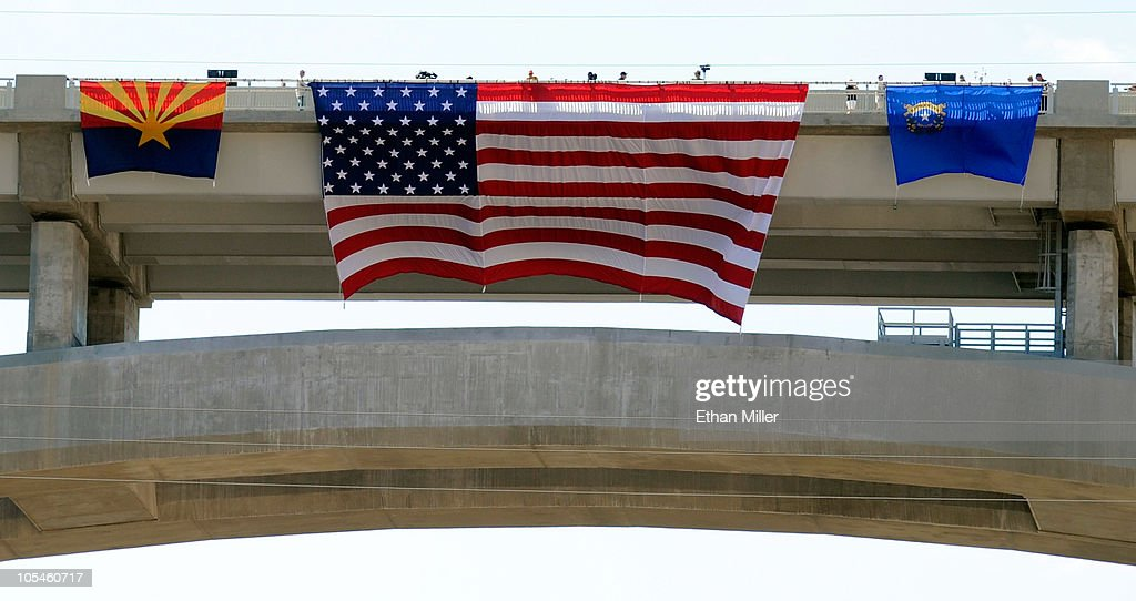 A state flag of Arizona, an American flag and a state flag of Nevada are hung over the side of the Mike O'Callaghan-Pat Tillman Memorial Bridge part of the Hoover Dam Bypass Project during a dedication ceremony October 14, 2010 in the Lake Mead National Recreation Area, Nevada. The 1,900-foot-long structure sits 890 feet above the Colorado River, about a quarter of a mile downstream from the Hoover Dam. The USD 240 million project to relieve vehicle traffic on the Hoover Dam began in 2003, and is scheduled to be open to traffic by next week.