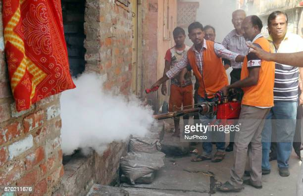 A state government health official fumigates an area to kill mosquitoes with a portable smoke fogger in order to combat Dengue in Kolkata Eastern...