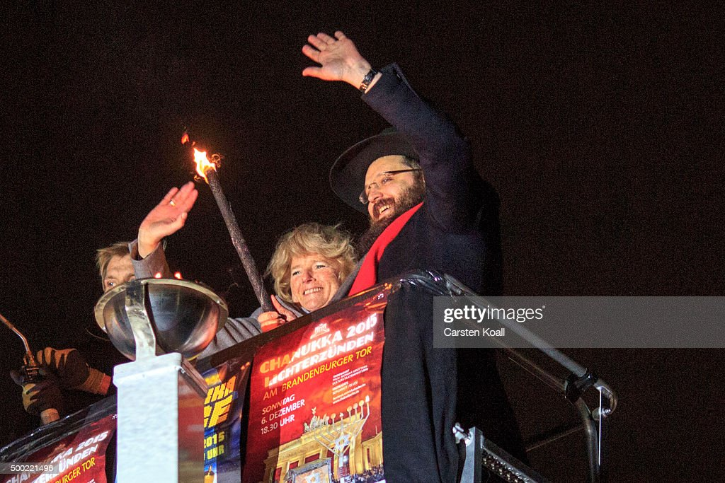 State Minister Monika Gruetters (C) and Rabbi Yehuda Teichtal (R) light the Hanukkah menorah lighting at a public Menorah ceremony near the Brandenburg Gate on December 6, 2015 in Berlin, Germany. The annual events are part of a worldwide Hanukkah campaign set into motion by the Lubavitcher Rebbe Rabbi Menachem M. Schneerson, of righteous memory.