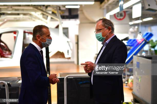 State Minister of Lower Saxony Stephan Weil speaks to Volkswagen CEO Herbert Diess on the first day of the resumption of automobile production at the...