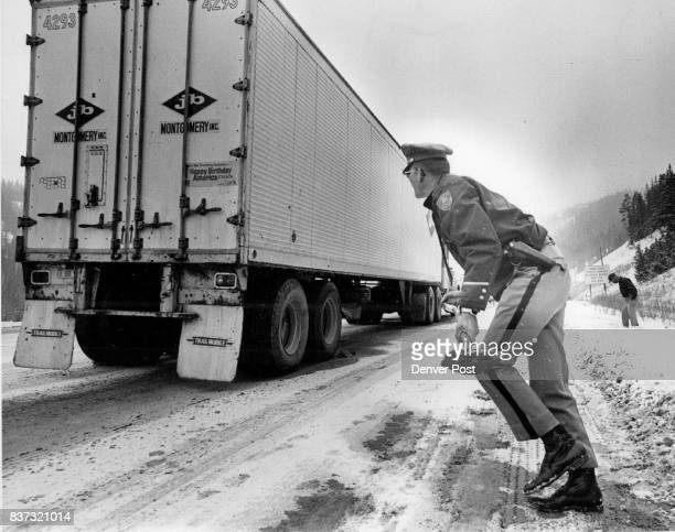State Patrolman Lyle Wohlers carries a shovelful of sand to a truck The sand was to keep the tires from spinning and the truck from sliding on the...