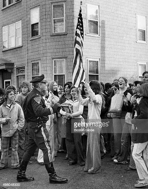 State police major Charles Gilligan officer orders young demonstrators one waving an American flag to leave the area in front of South Boston High...